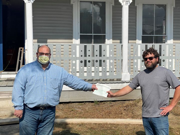 (From left) RuralEdge Executive Director Patrick Shattuck, landlord Tyler Hebert, and RuralEdge Homeownership Center Director Dawn Cross pose for a picture celebrating the first Re-Housing Recovery Programs distributed in the Northeast Kingdom.