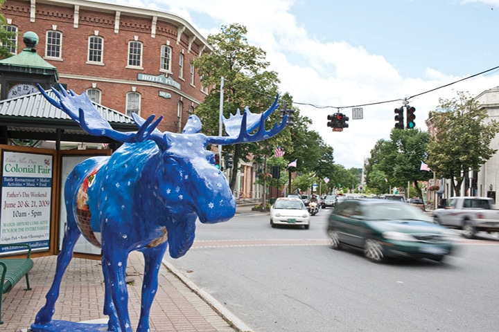Downtown street with blue moose statue in foreground