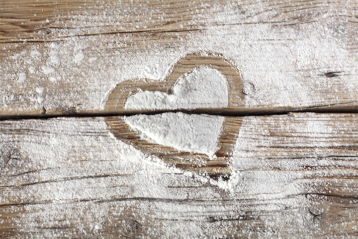 A heart shape is drawn in flour on a table