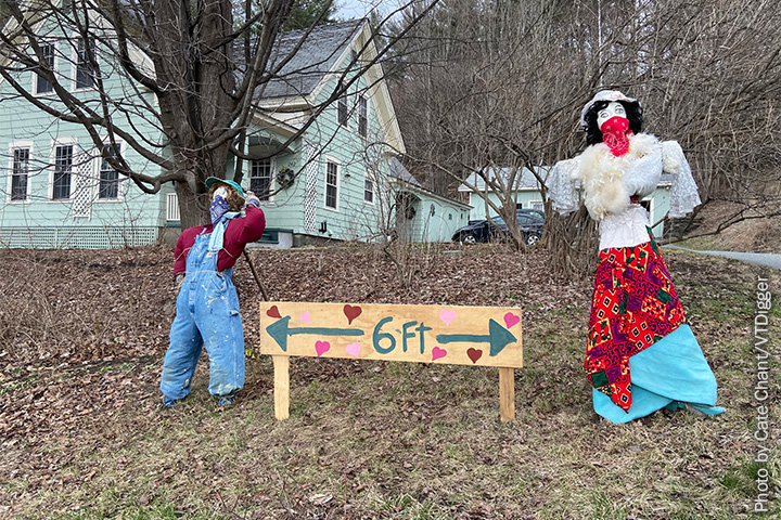 "A scarecrow and a mannequin with a sign saying ""6 FT"" between them and a tree and house behind them"