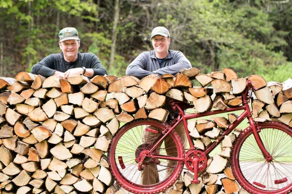 Two men lean on pile of stacked wood
