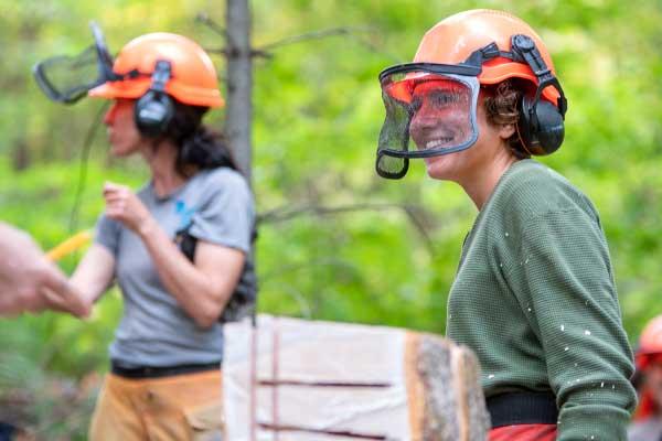 Two women wearing forestry helmets