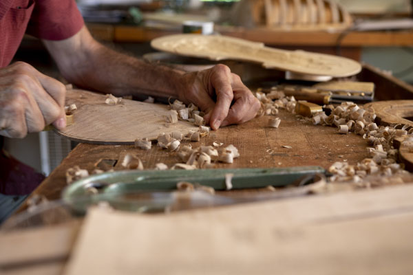 Man's hands on a table chiseling a piece of wood
