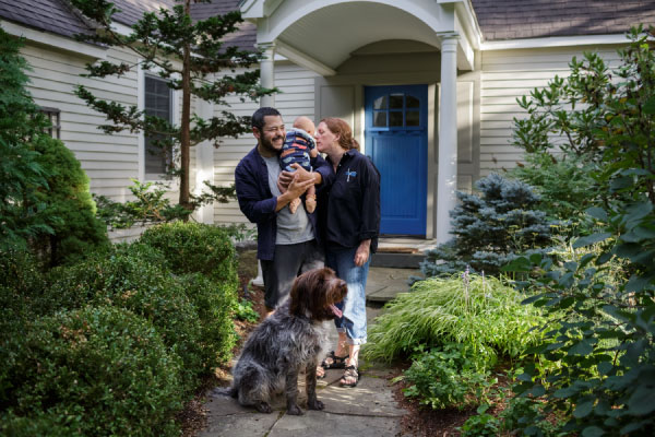 A man holding a abby and a woman standing in a doorway with a dog sitting at their feet